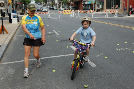 Young bicyclist with instructor Betty Kelly